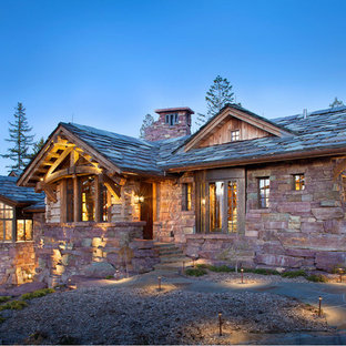 Large mountain style brown stone exterior home photo in Other