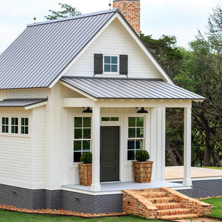 Modelo de fachada de casa blanca, de estilo de casa de campo, de tamaño medio, de dos plantas, con revestimiento de vinilo, tejado a dos aguas y tejado de metal