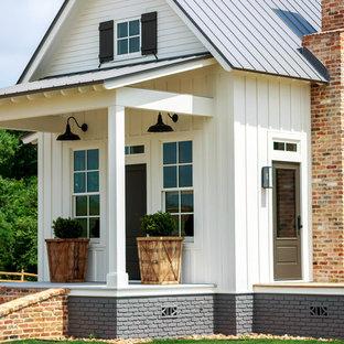 На фото: двухэтажный, белый мини дом среднего размера в стиле кантри с облицовкой из винила, двускатной крышей и металлической крышей с