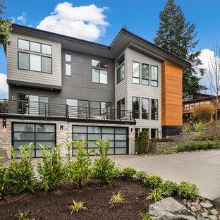 Bild på ett stort funkis grått hus, med tre eller fler plan, blandad fasad, platt tak och tak i mixade material