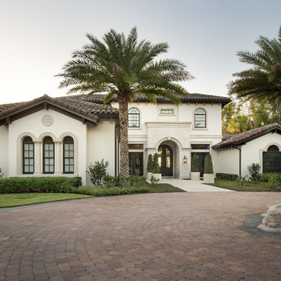 Tuscan beige two-story exterior home photo in Orlando with a tile roof