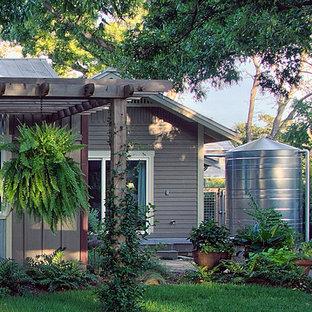 Ispirazione per la facciata di una casa unifamiliare piccola marrone american style a un piano con rivestimento con lastre in cemento, tetto a capanna e copertura in metallo o lamiera