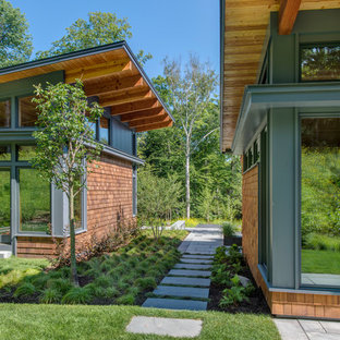 Small contemporary brown one-story wood exterior home idea in Burlington with a shed roof