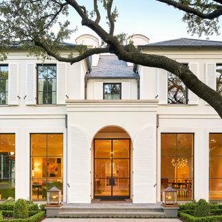 Inspiration för ett stort vintage beige hus, med två våningar, stuckatur, valmat tak och tak i shingel