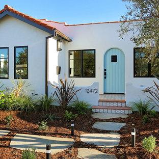 Imagen de fachada de casa blanca, tradicional renovada, pequeña, de una planta, con revestimiento de estuco, tejado a dos aguas y tejado de teja de barro