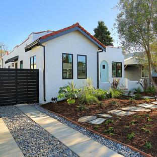 Modelo de fachada de casa blanca, tradicional renovada, pequeña, de una planta, con revestimiento de estuco, tejado a dos aguas y tejado de teja de barro