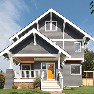 This is an example of a large arts and crafts grey house exterior in Seattle with three or more storeys, wood siding, a gable roof and a shingle roof.