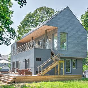 Modern inredning av ett mellanstort grått hus, med två våningar och tak i metall