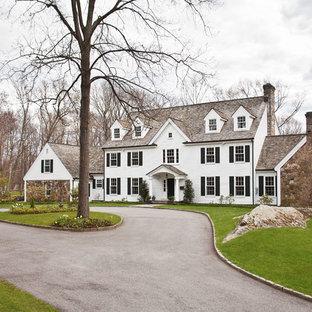 Ejemplo de fachada blanca, clásica renovada, extra grande, de tres plantas, con revestimientos combinados y tejado a dos aguas