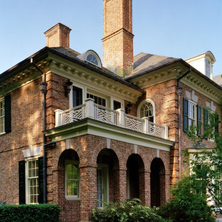 Huge elegant red three-story brick house exterior photo in New York with a hip roof and a shingle roof
