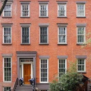 Foto della facciata di una casa a schiera rossa classica a tre o più piani con rivestimento in mattoni e tetto piano