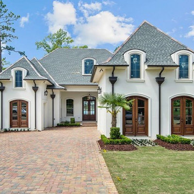 Inspiration for a mid-sized timeless white one-story stucco house exterior remodel in New Orleans with a hip roof and a shingle roof