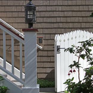 Ejemplo de fachada de casa gris, tradicional, de tamaño medio, de dos plantas, con revestimiento de madera y tejado a doble faldón