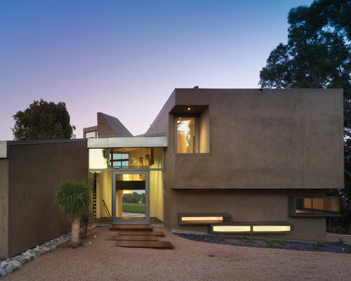 Example of a mid-sized trendy beige two-story stucco exterior home design in