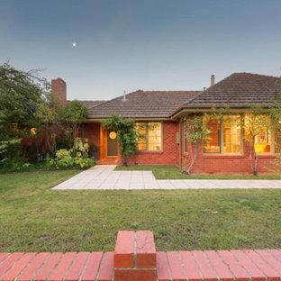 Ejemplo de fachada de casa roja, retro, grande, de una planta, con revestimiento de ladrillo, tejado a dos aguas y tejado de teja de barro