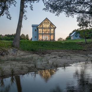 Lantlig inredning av ett stort vitt hus, med två våningar, sadeltak och tak i metall