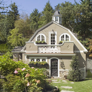 Inspiration for a mid-sized rustic beige two-story mixed siding exterior home remodel in Boston with a gambrel roof and a shingle roof