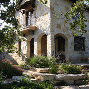 Example of a tuscan stone exterior home design in Austin