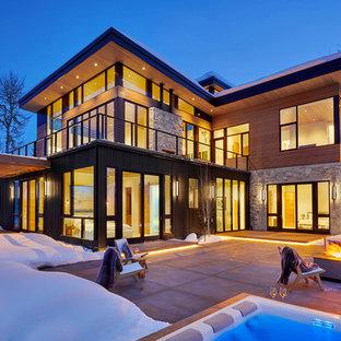 Idée de décoration pour une grand façade de maison multicolore design à un étage avec un toit plat et un toit végétal.