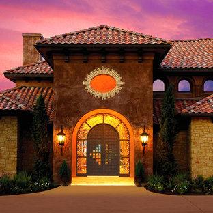 Imagen de fachada marrón, mediterránea, extra grande, a niveles, con revestimiento de piedra y tejado a cuatro aguas