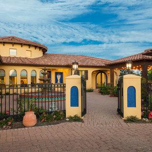 Diseño de fachada amarilla, de estilo americano, de dos plantas, con revestimiento de estuco y tejado a dos aguas