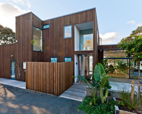 Example of a trendy brown split level wood flat roof design in hamilton