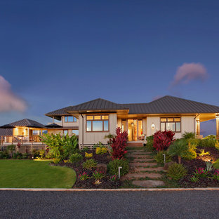 Example of a mid-sized island style beige two-story glass exterior home design in Hawaii