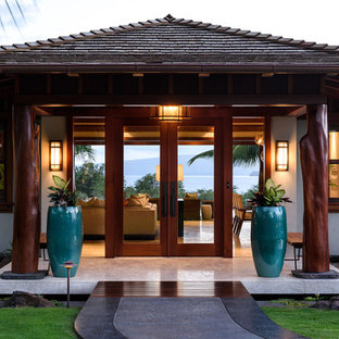 Large tropical beige one-story stucco exterior home idea in Hawaii