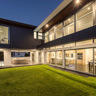 This is an example of a large contemporary two-storey black house exterior in Brisbane with concrete fiberboard siding, a flat roof and a metal roof.