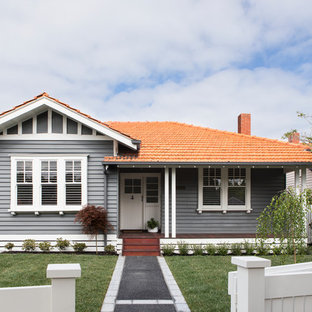 Design ideas for a traditional two-storey grey house exterior in Melbourne with wood siding, a gable roof and a tile roof.