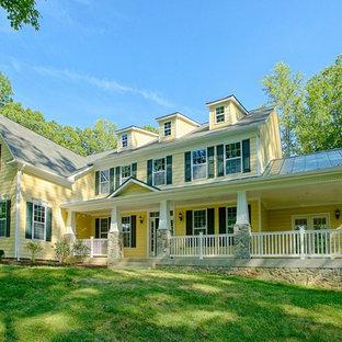 ワシントンD.C.のトラディショナルスタイルのおしゃれな家の外観 (黄色い外壁、ビニールサイディング、混合材屋根) の写真