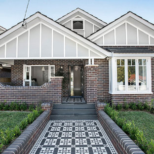Mid-sized transitional two-storey brick multi-coloured house exterior in Sydney with a gable roof and a tile roof.