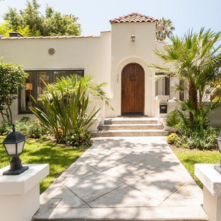 Mid-sized tuscan one-story adobe house exterior photo in Los Angeles with a tile roof