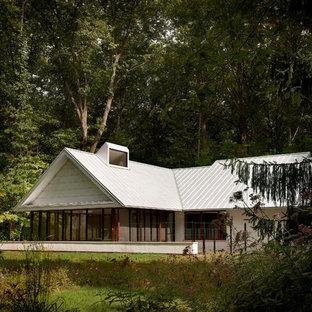 Modelo de fachada blanca, industrial, pequeña, de dos plantas, con revestimiento de estuco y tejado a dos aguas