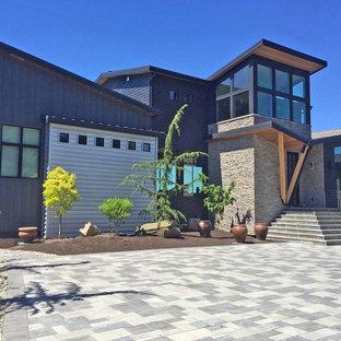 Modelo de fachada de casa azul, actual, grande, de dos plantas, con revestimiento de metal, tejado de un solo tendido y tejado de teja de madera