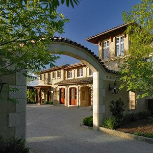 Diseño de fachada beige, mediterránea, a niveles, con revestimiento de estuco