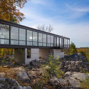 Idee per la facciata di una casa unifamiliare grande beige contemporanea a due piani con rivestimento in vetro, tetto piano e copertura in metallo o lamiera