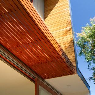 Foto de fachada de casa beige, vintage, de dos plantas, con revestimiento de madera, tejado plano y tejado de metal
