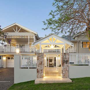 Large beach style two-storey beige house exterior in Brisbane with wood siding and a gable roof.