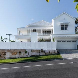 Modelo de fachada de casa blanca, costera, de dos plantas, con revestimiento de vinilo, tejado a cuatro aguas y tejado de metal