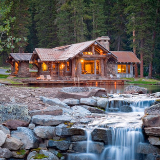 Mountain style stone exterior home photo in Other
