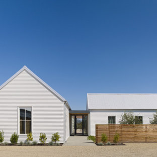 Example of a large farmhouse white one-story wood gable roof design in San Francisco