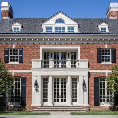 Traditional red three-story brick house exterior idea in New York with a hip roof and a shingle roof