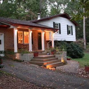 Example of a small eclectic white split-level concrete fiberboard exterior home design in Other
