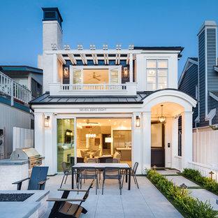 Ispirazione per la facciata di una casa unifamiliare stile marinaro a due piani con copertura in metallo o lamiera