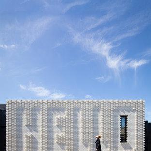 Foto della facciata di una casa piccola bianca contemporanea a un piano con rivestimento in mattoni e tetto piano