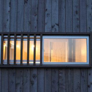 Ejemplo de fachada de casa gris, costera, pequeña, a niveles, con revestimiento de madera, tejado a dos aguas y tejado de metal