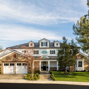 Inspiration for a large timeless white two-story exterior home remodel in Orange County with a hip roof and a shingle roof