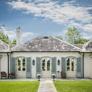 Mid-sized traditional white one-story stucco exterior home idea in Birmingham with a hip roof