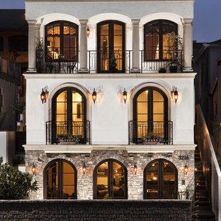 Идея дизайна: большой, бежевый, четырехэтажный дом в средиземноморском стиле с комбинированной облицовкой